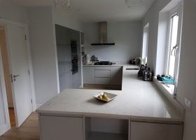 Light Grey Cabinets with Tall Dust Grey Cabinets and a Quartz Worktop